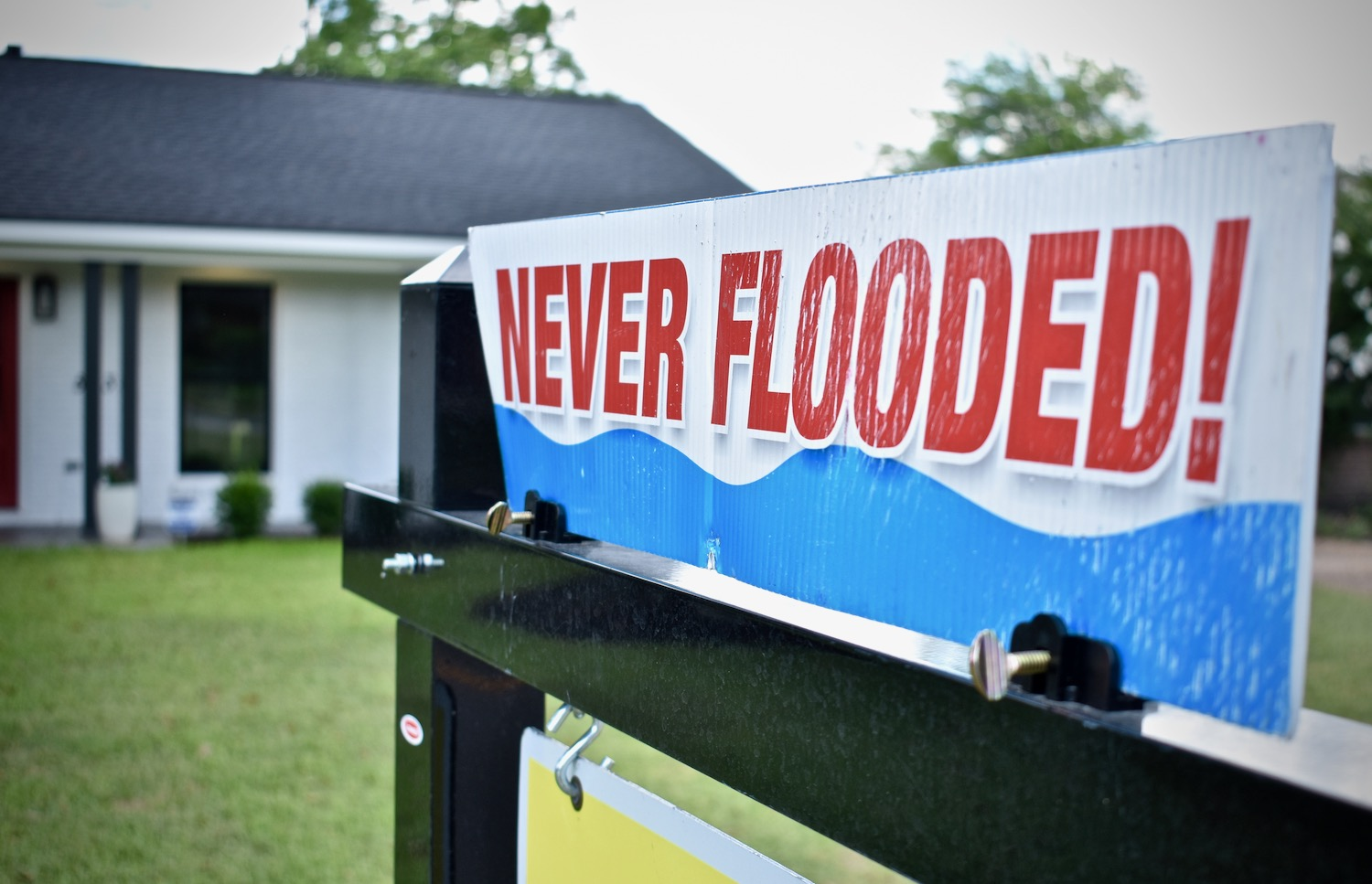 "A for sale sign in front of a home that says ""Never Flooded"" in Meyerland and Bellaire, TX"