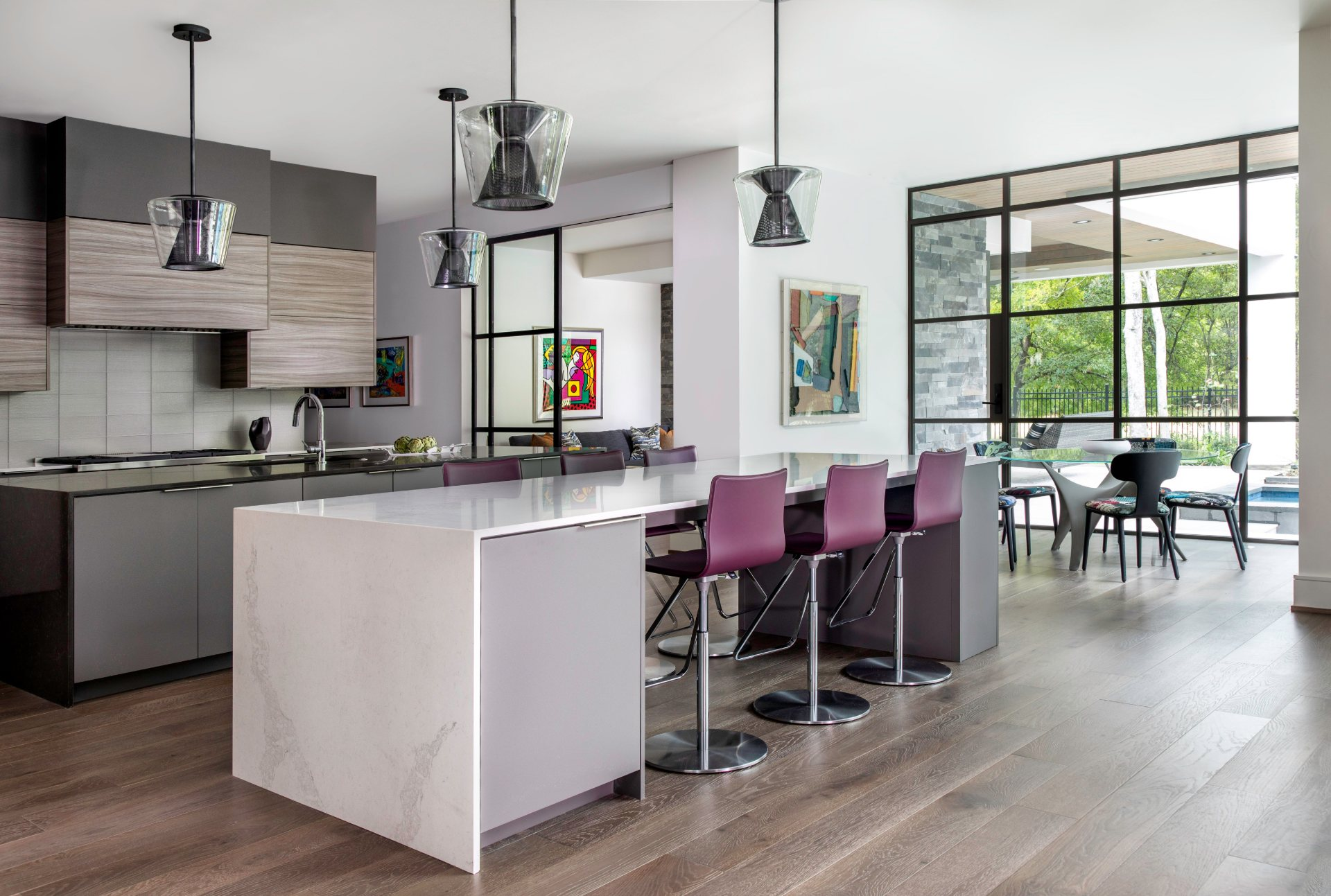 Modern kitchen with plum bar stools, two marble islands and elegant light fixtures
