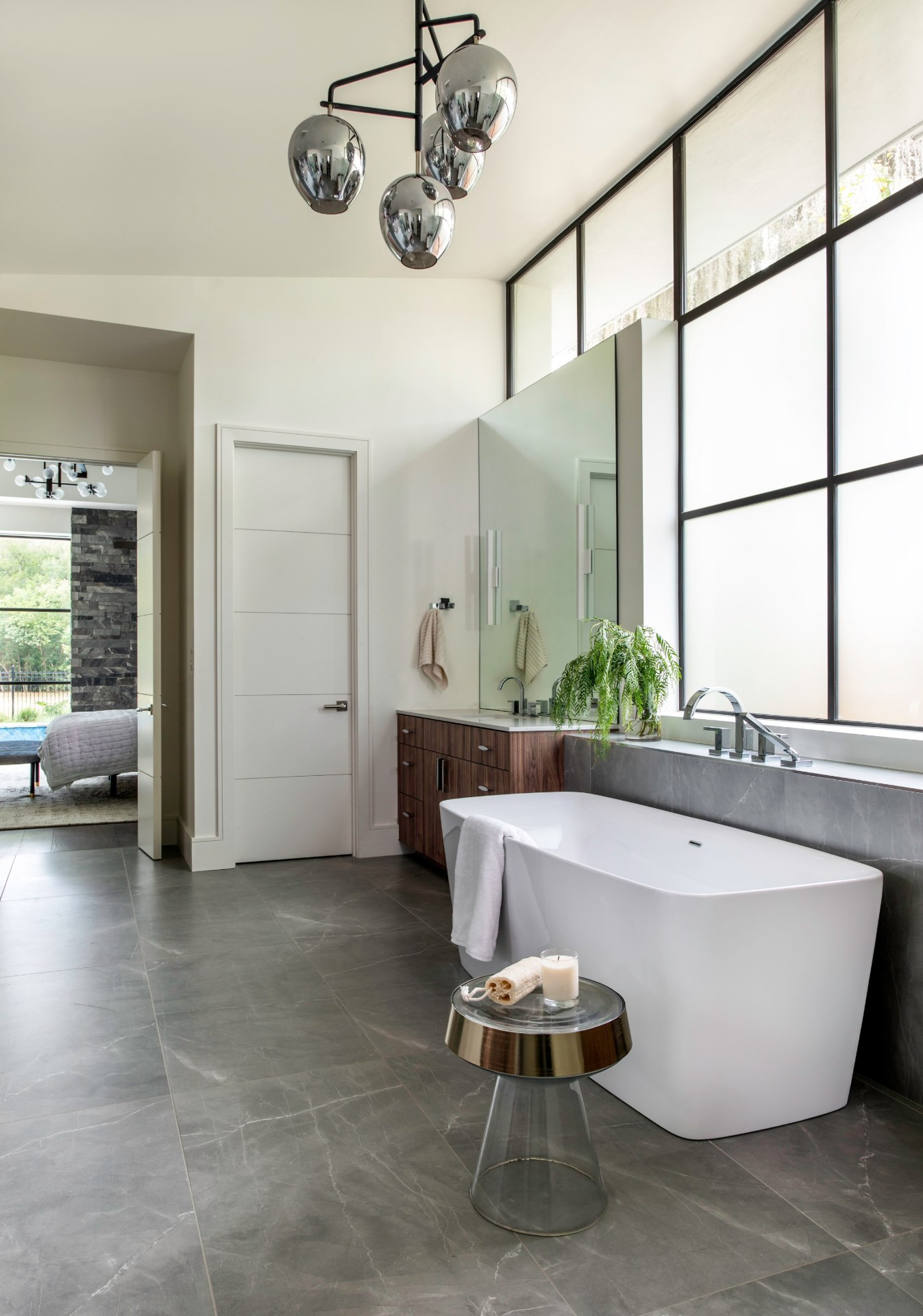 Master bathroom featuring gray stone floors and massive windows